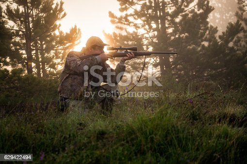 Portrait of hunter aiming with sniper rifle in the forest.