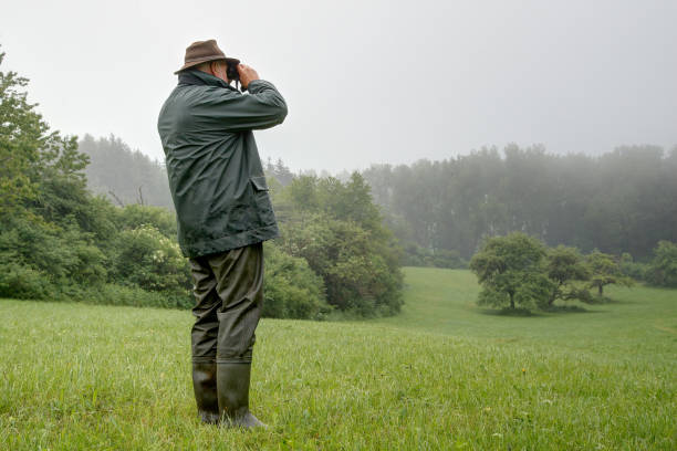 Hunter in the rain, watch a small idyllic valley through his binoculars. stock photo