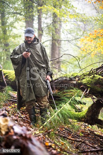 Hunter with rifle and satellite phone standing in the forest next to fallen tree.