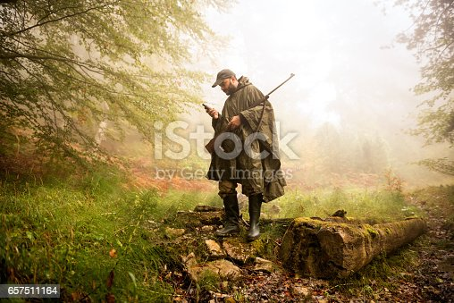 Hunter in the forest with a rifle standing next to fallen tree and calling for others over satllite phone.