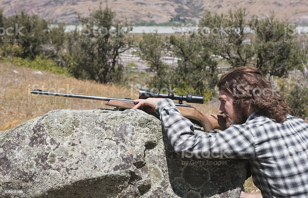 Hunter looking through the scope rifle stock photo