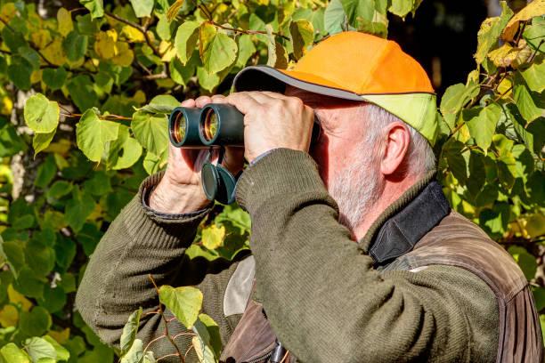 Hunter looks through his binoculars. stock photo