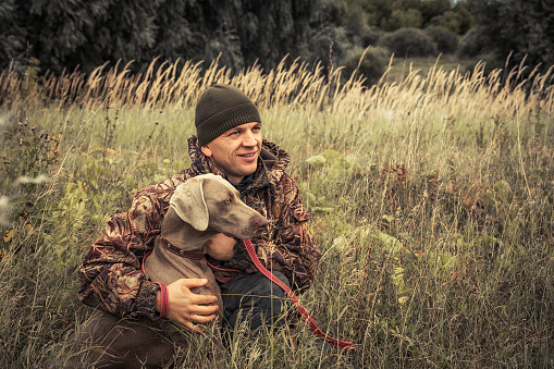 Hunter man with hunting dog Weimaraner portrait in tall grass in rural field during hunting season