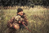 istock Hunter man with hunting dog Weimaraner in tall grass in rural field during hunting season 1270305931