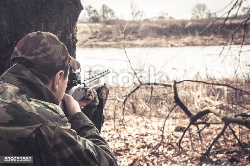 istock Hunter man with shotgun aiming  to make shot during hunt 539653582