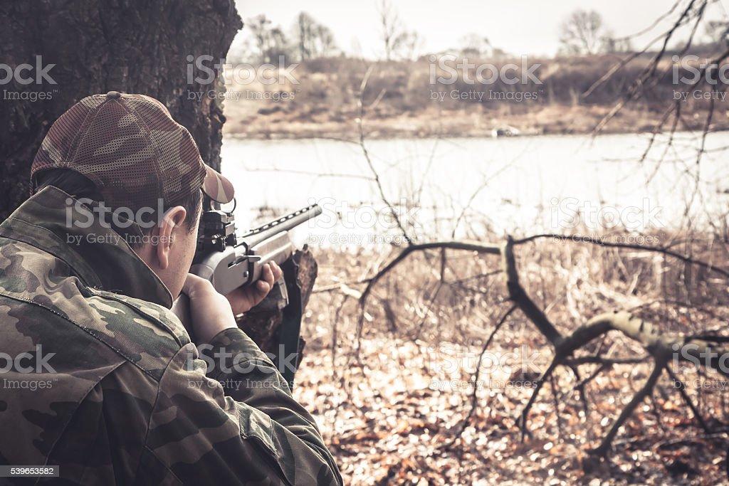 Hunter man with shotgun aiming  to make shot during hunt stock photo