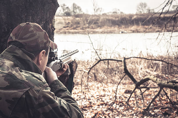 Hunter man with shotgun aiming  to make shot during hunt Man with gun prepared to shot  in rural field during hunting season ambush stock pictures, royalty-free photos & images