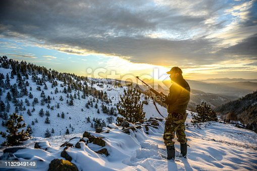 Huntsman standing on a snow-capped mountain ridge and observing a wonderful sunset.