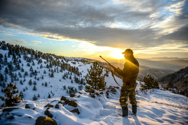 Hunter observing a beautiful vista while standing on a mountain ridge covered with snow Huntsman standing on a snow-capped mountain ridge and observing a wonderful sunset. hunter stock pictures, royalty-free photos & images