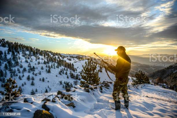 Photo of Hunter observing a beautiful vista while standing on a mountain ridge covered with snow