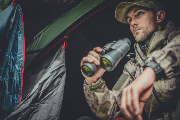 Hunter Spotting Wildlife Caucasian Hunter Spotting Wildlife From His Tent in Remote Place. poaching animal welfare stock pictures, royalty-free photos & images