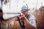 Hunter Stalking And Aiming His Rifle At Prey