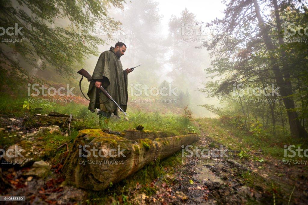 Hunter standing on fallen tree stock photo