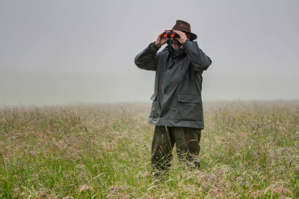 Hunter stands with rainwear in the high meadow. stock photo