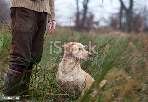 Hunting dog sits near the foot of the hunter