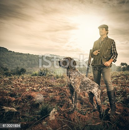Hunter with German Shorthaired pointer in abandoned field during the morning
