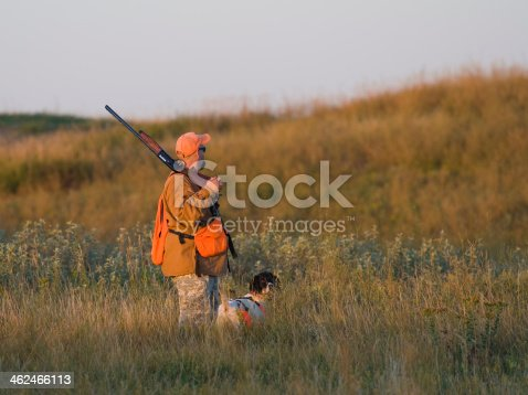 A hunter out on the prairie in the early morning sun with his dog