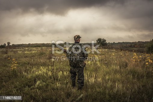 Hunter with hunting ammunition gun going through rural field during hunting season in overcast rainy day