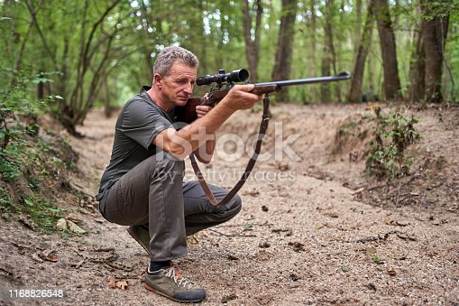 Hunter with rifle in the forest