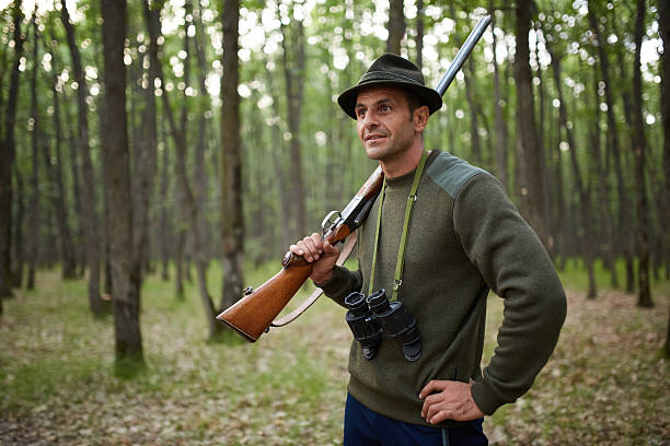 Hunter with shotgun in the forest Hunter with double barrel shotgun in the forest park ranger stock pictures, royalty-free photos & images