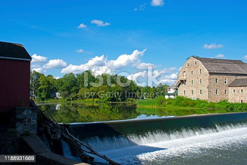 Scenic view of the exterior of the Hunterdon Art Museum in Clinton, New Jersey, on a sunny day, with a waterfall in the foreground