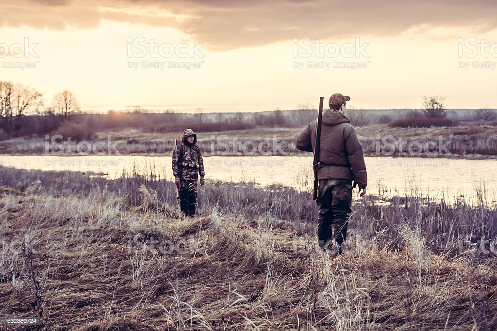 Hunters choosing good position  for hunting in field nearby river stock photo
