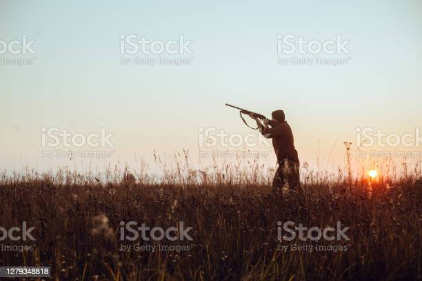 Photo of Hunter's dark silhouette with blue sky and red sun - photo with selective focus