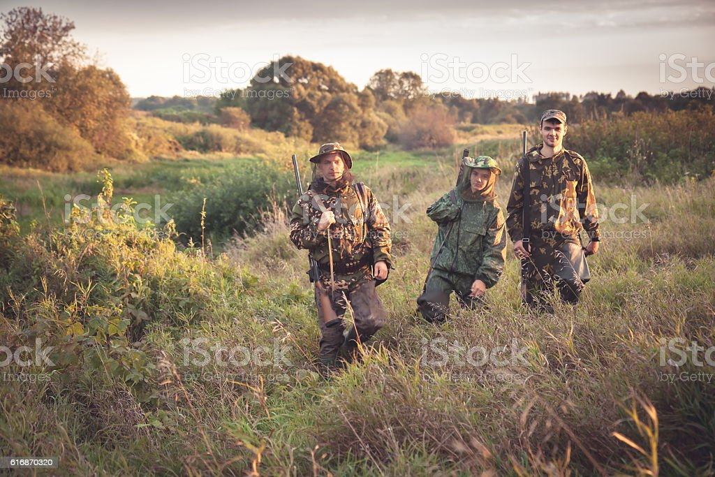 Hunters going through tall garass in rural field at dawn stock photo