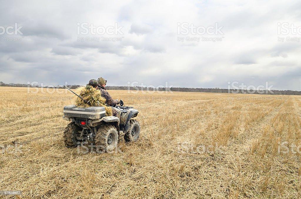 Hunters on quad bikes. stock photo