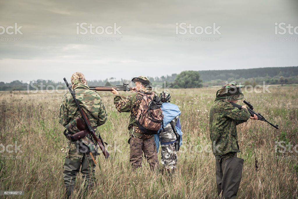 Hunters preparing for hunting in rural field in overcast day stock photo