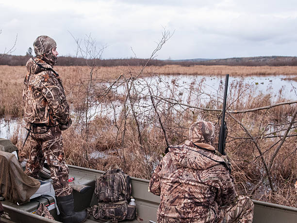 Hunters Waiting for Migatory Birds Glenelg, Canada - November 4, 2011: Hunters in full camouflage wait patiently from their hunting blind on the St. Mary's River for the arrival of migratory Canada geese and ducks.  hunting blind stock pictures, royalty-free photos & images