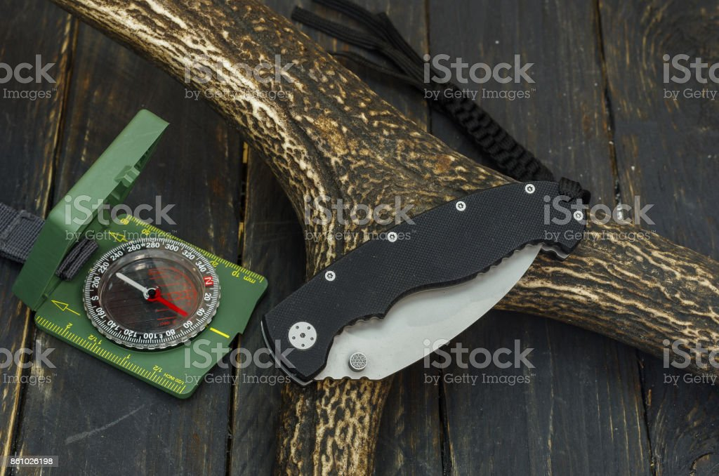Hunting composition of a folded knife, a compass and a deer horn. stock photo