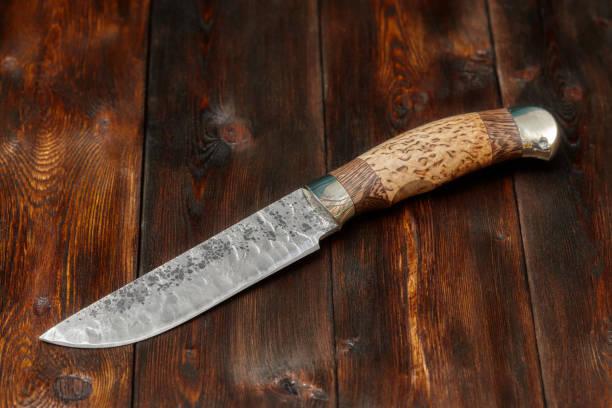damast jagdmesser handarbeit auf hölzernen hintergrund - damaststahl stock-fotos und bilder