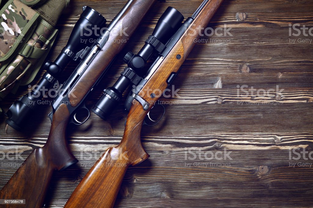 Hunting equipment on old wooden background. Hunting rifle and ammunition on a dark wooden background.Top view. Ammunition Stock Photo