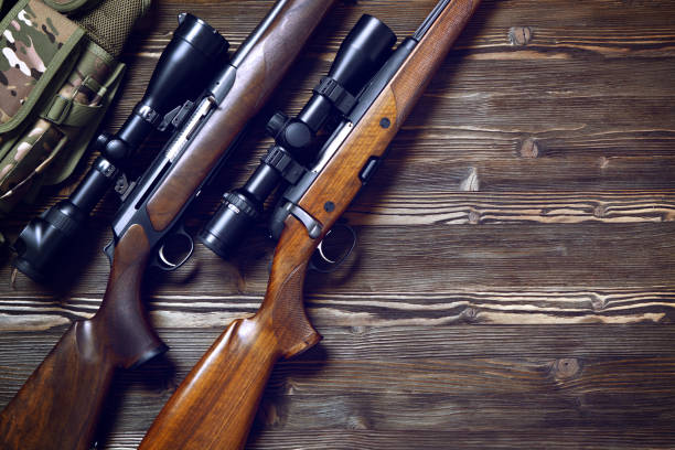Hunting equipment on old wooden background. Hunting rifle and ammunition on a dark wooden background.Top view. hunter stock pictures, royalty-free photos & images