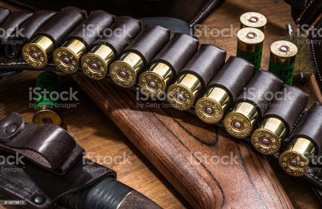 Hunting equipment - pump action shotgun, 12 guage cartridge end hunting knife on the wooden table. stock photo