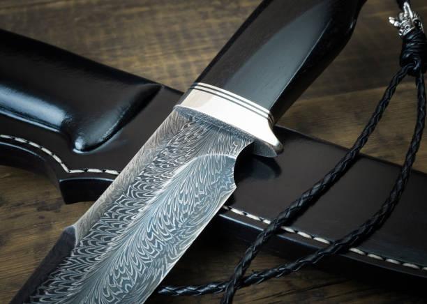 jagdmesser aus damaskus mosaik mit mammut-stoßzahn auf einem schwarzen hintergrund. handgefertigte lederscheide - damaststahl stock-fotos und bilder