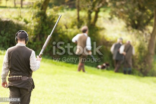 Four men, in a shooting party, walking across a meadow, holding their shotguns, Devon, UK