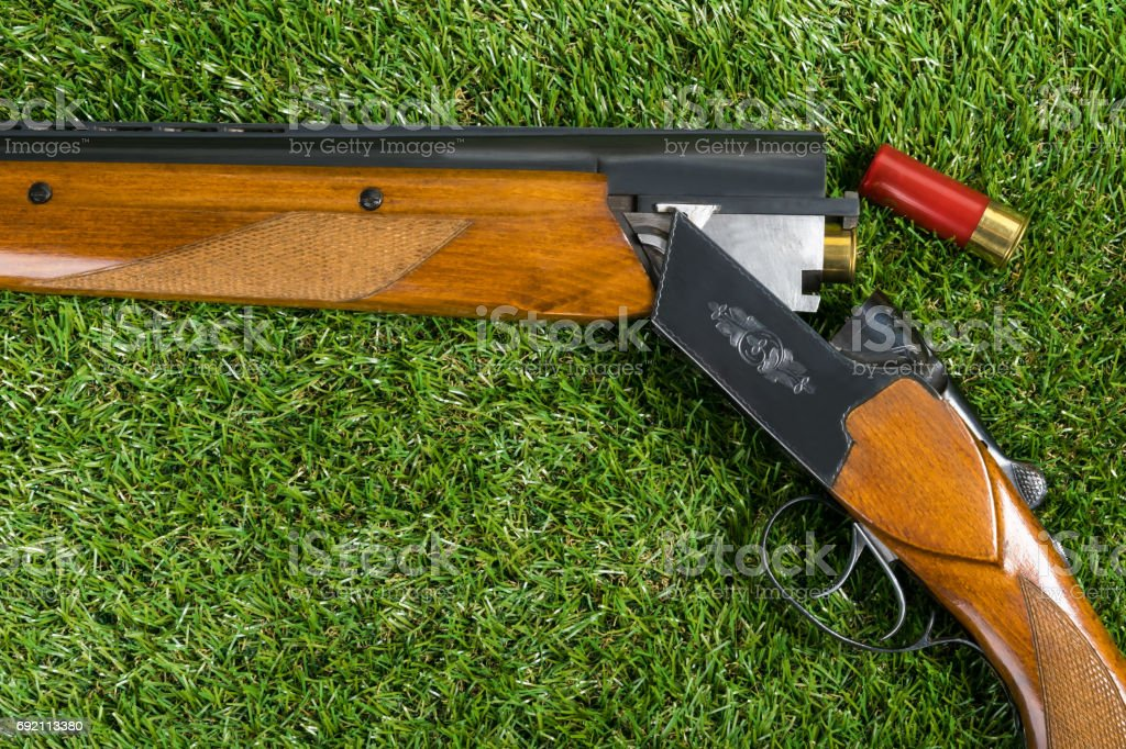 hunting rifle with a red cartridge lies on the grass stock photo
