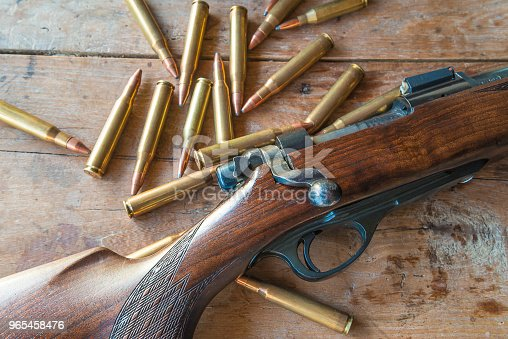Hunting gun with bullets on old wooden background