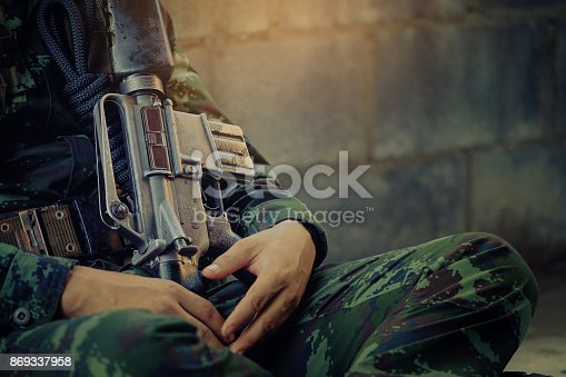 istock hunting, war, army and people concept - young soldier, ranger or hunter with gun sitting and sleeping, Soldier sits near a brick wall. 869337958