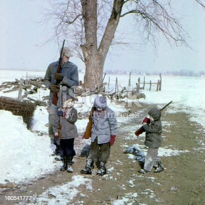 Young boys going hunting with Grandad. Grandad has a Winchester model 12 shotgun, boy on left has Daisy model 25 BB gun, middle boy has Winchester model 67 rifle, boy on right has pop gun. Iowa 1959, scanned film with grain.