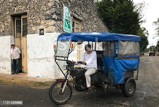 Hunucmá, Yucatan, Mexico: A blue pedicab passes a house with a senior man in the doorway in the town of Hunucmá, 25 kilometers from Merida in the Yucatan Peninsula, Mexico.