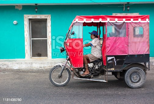 Hunucmá, Yucatan, Mexico: A red pedicab passes a vibrant turquoise house in the town of Hunucmá, 25 kilometers from Merida in the Yucatan Peninsula, Mexico.