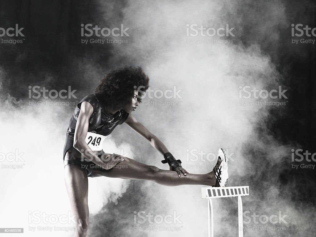 A hurdler stretching stock photo