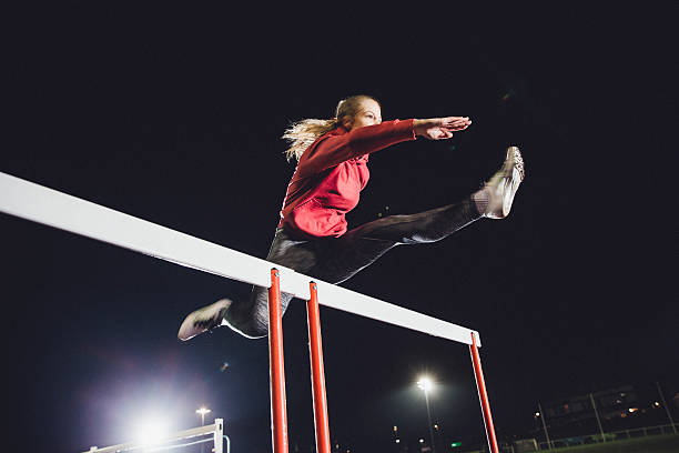 Hurdling Young Athlete Young female athlete doing hurdle race training on a running track at dusk. women's track stock pictures, royalty-free photos & images