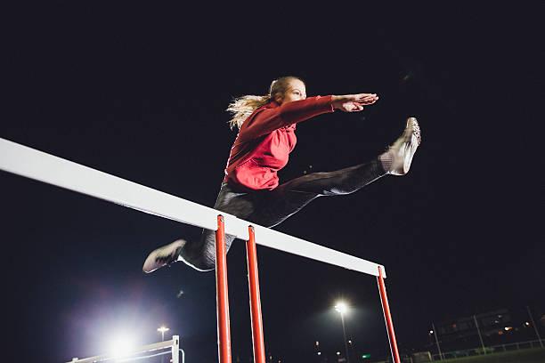 hurdling young athlete - corsa su pista femminile foto e immagini stock