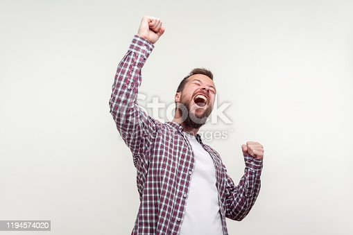 Hurray! Portrait of overjoyed winner, bearded man in casual plaid shirt raising hands, screaming yes i did it, emotionally reacting to success, victory. indoor studio shot isolated on white background