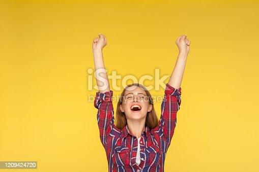 Hurray, victory! Portrait of delighted girl in checkered shirt yelling for happiness, enjoying life, rejoicing success with arms raised, celebrating triumph. studio shot isolated on yellow background