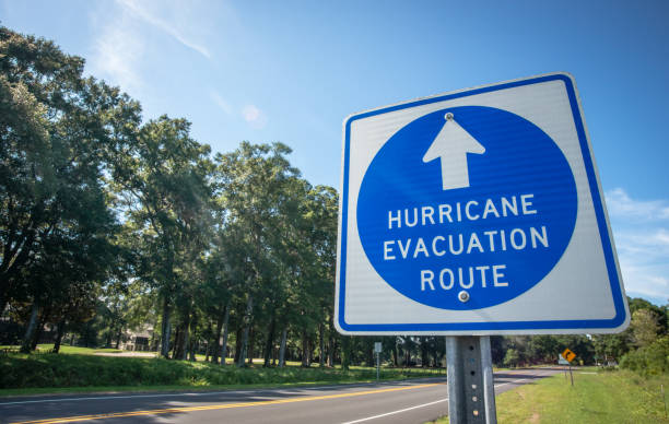 Hurricane Evacuation Route Sign A sign directs hurricane evacuees to safety. making stock pictures, royalty-free photos & images